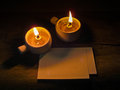Candle and paper on old wooden background Royalty Free Stock Photos