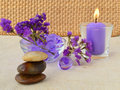 Candle and purple flowers aromatic relaxation aroma therapy spa concept Stock Image