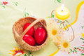 Candle and red eggs yellow three in small basket for easter Stock Image