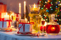 Candlelight and gifts all around the christmas table in home Stock Photos