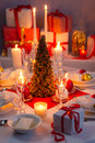 Candlelight wafer and gifts on the christmas table in home Stock Photo