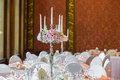 Candles burning in a chandelier on elegant dinner table Royalty Free Stock Photo