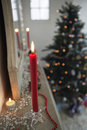 Candles burning on mantelpiece on christmas day closeup of with tree in background Royalty Free Stock Image