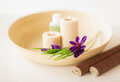 Candles and iris flowers in wooden bowel and mat Royalty Free Stock Images