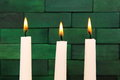Candles lit up against the wooden green background Royalty Free Stock Photo