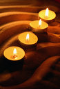 Candles on sand few lighting in a row dark background Royalty Free Stock Photography