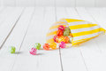 Candy bag spilling the candies over a white table yellow striped its wooden Stock Photo