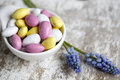Candy bonbons bowl with bright pink yellow and white sweet and hyacinth flowers Royalty Free Stock Photos