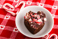 Candy cane fudge heart shaped piece of on small round white plate with canes Royalty Free Stock Image