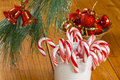 Candy canes at christmas in a mug beneath a tree decorations in background Royalty Free Stock Photo