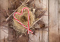 Candy canes in the shape of a heart on a nest resting rustic wooden background Stock Photography
