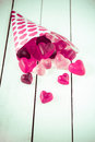 Candy cone spilling gummy candies over a table close up view of decorated with pink hearts heart shaped white wooden board Stock Photo
