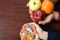Candy and fruit being held Royalty Free Stock Photo