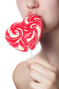 Candy red heart on the lips of a girl close up Stock Image