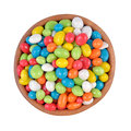 Candy sea pebbles in a wooden bowl on a white background isolated Royalty Free Stock Photos