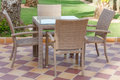 Cane furniture outdoor patio with glass table and chairs on tiled floor Royalty Free Stock Photo