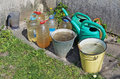 Canisters, buckets and watering cans with water are found near t Royalty Free Stock Photo