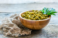 Canned green peas in a wooden bowl. Royalty Free Stock Photo