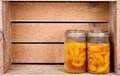 Canned peaches in a rustic crate Royalty Free Stock Photo