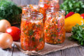 Canned vegetable salad in glass jars and ingredients for homemade Royalty Free Stock Photo
