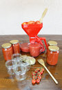 Canning fresh crushed tomato sauce strainer empty and full jars wooden spoon and cherry tomatoes on wooden table Stock Photos