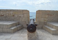 A cannon is aimed towards alicante harbour from the castle above Stock Image