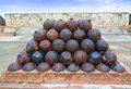 Cannon balls stack of old rusty colonial on historic military fort walls Royalty Free Stock Image