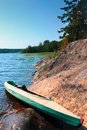 Canoe on the lake shore at camp of beautiful at summer day under blue sky with light clouds Stock Image