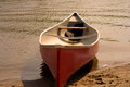 Canoe red parked by the sand in a south florida beach view of the water and sand Stock Images