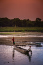 Canoe on a river two young boys crossing the in small wooden in royal chitwan national park in terai – nepalese lowlands Royalty Free Stock Photo