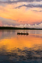 Canoe at sunrise malagasy people crossing the inlets in an outrigger on april near nosy be madagascar Stock Images
