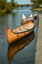 Canoes attach to a quay with a bridge and a blue sky Royalty Free Stock Images