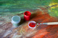 Cans of paint and brush on painted art linen two paintbrush are lying the are Stock Image