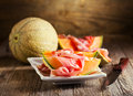 Cantaloupe melon with prosciutto on wooden background Stock Image