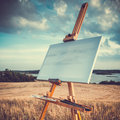 Canvas rests on a easel on lake landscape blank retro stylized Stock Photos