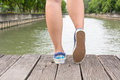 Canvas sneakers on feet on the wooden bridge