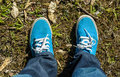 Canvas sneakers with jeans top view blue color on old grass ground natural Royalty Free Stock Photos