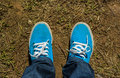 Canvas sneakers with jeans top view blue color on old grass ground natural Royalty Free Stock Photo