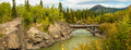 Canyon creek bridge panoramic composition of wooden log across aishihik river along original alaskan highway in the yukon Royalty Free Stock Image