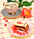 Cap of coffee, a rose and a cake on tablecloth Royalty Free Stock Photo