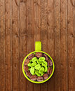 Cap with green and roasted coffee beans on wooden background Royalty Free Stock Photos