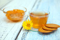 The cap of tea with coocies and orange jam marguerite flower Stock Image