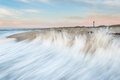 Cape hatteras lighthouse and national seashore north carolina a wave from the atlantic ocean slams the beach at s with the Stock Photography