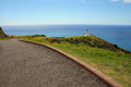 Cape reinga lighthouse in the distance located north edge of new zealand is seen with path leading to it Stock Image