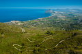 Cape san vito and cafano bay sicily ws winding mountain road in front of sweeping view across to north west housing farms side by Stock Photo