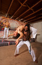 Capoeira back bending performer holding partner in over shoulders Royalty Free Stock Photos