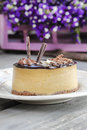 Cappuccino cake on white plate purple flowers in the background selective focus Royalty Free Stock Image
