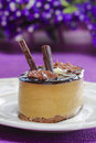 Cappuccino cake on white plate purple flowers in the background selective focus Stock Photo