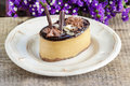 Cappuccino cake on white plate purple flowers in the background selective focus Royalty Free Stock Photography