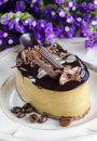Cappuccino cake on white plate purple flowers in the background selective focus Royalty Free Stock Photos